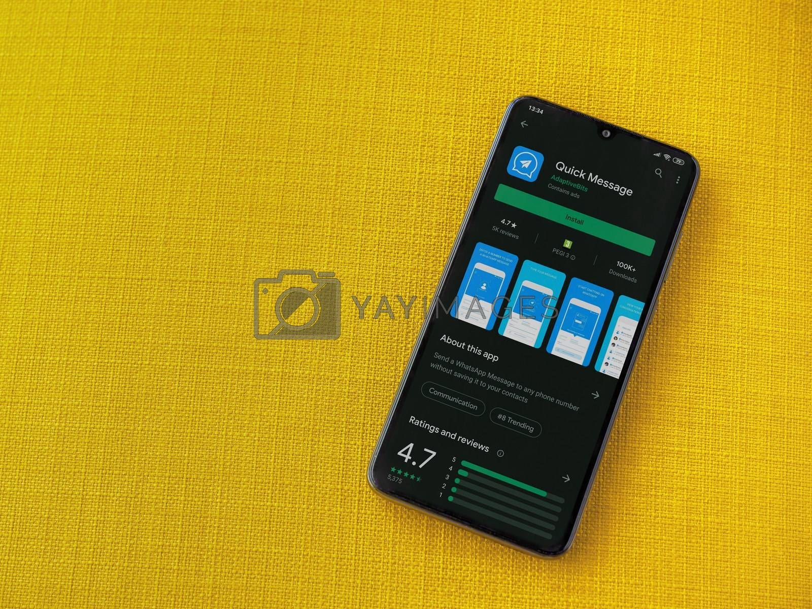 Lod, Israel - July 8, 2020: Quick Message app play store page on the display of a black mobile smartphone on a yellow fabric background. Top view flat lay with copy space.