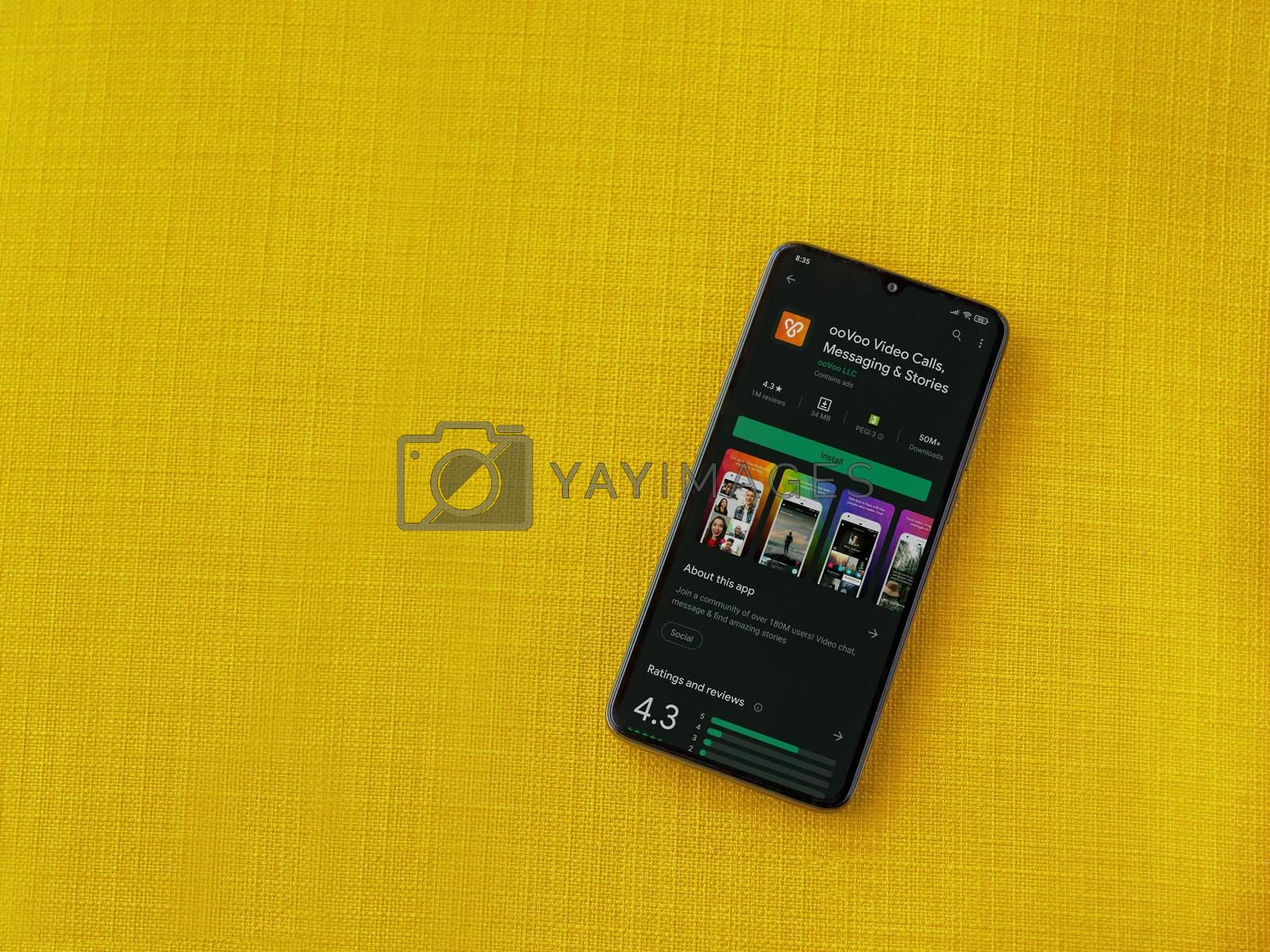 Lod, Israel - July 8, 2020: ooVoo app play store page on the display of a black mobile smartphone on a yellow fabric background. Top view flat lay with copy space.