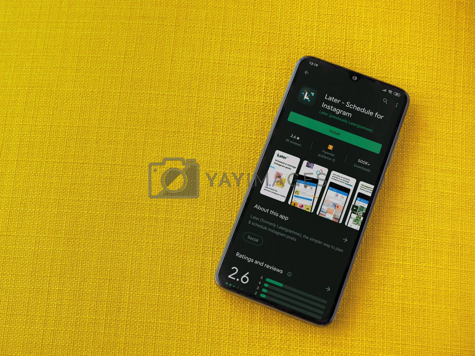 Lod, Israel - July 8, 2020: Later app play store page on the display of a black mobile smartphone on a yellow fabric background. Top view flat lay with copy space.