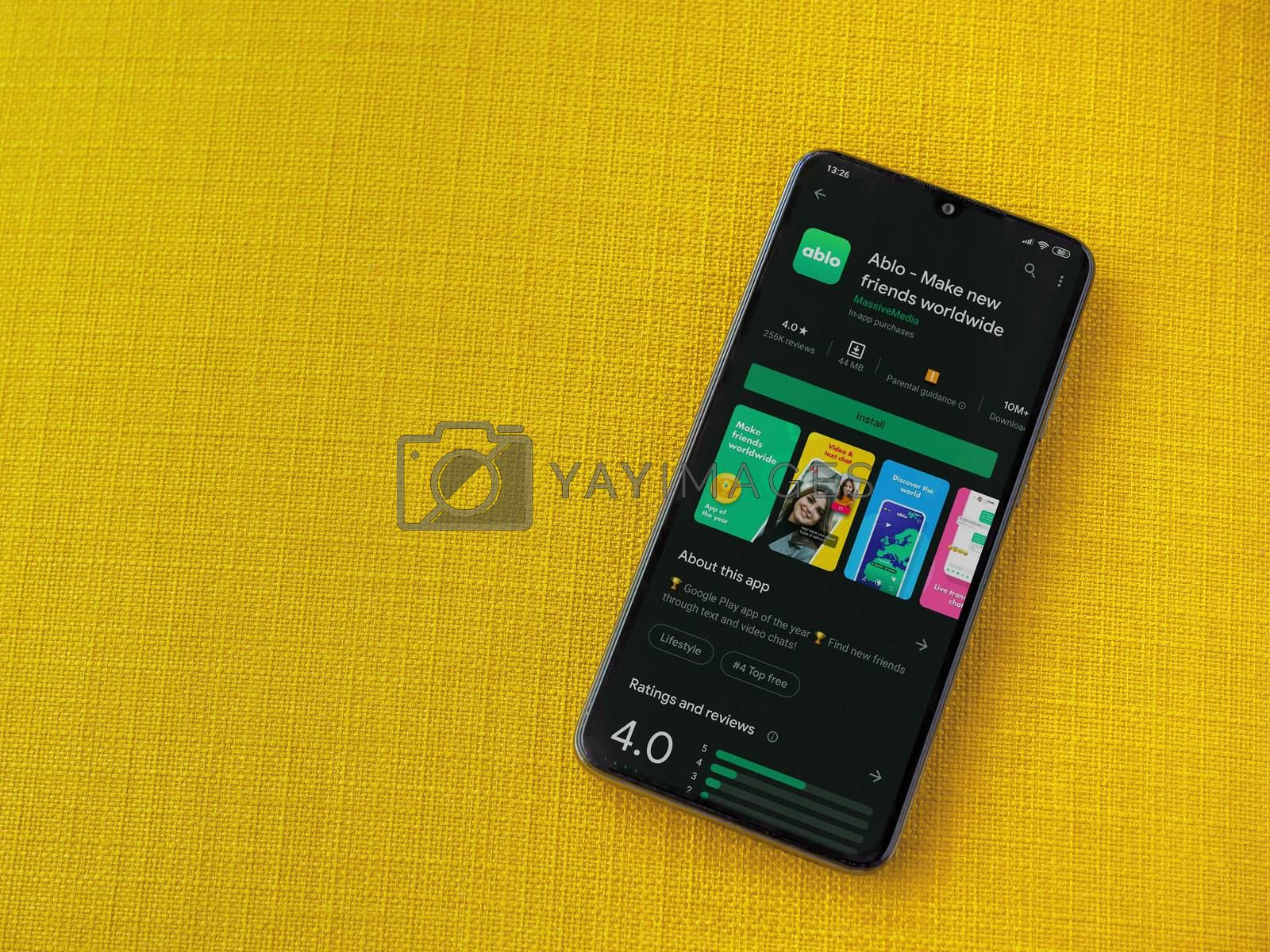 Lod, Israel - July 8, 2020: Ablo app play store page on the display of a black mobile smartphone on a yellow fabric background. Top view flat lay with copy space.