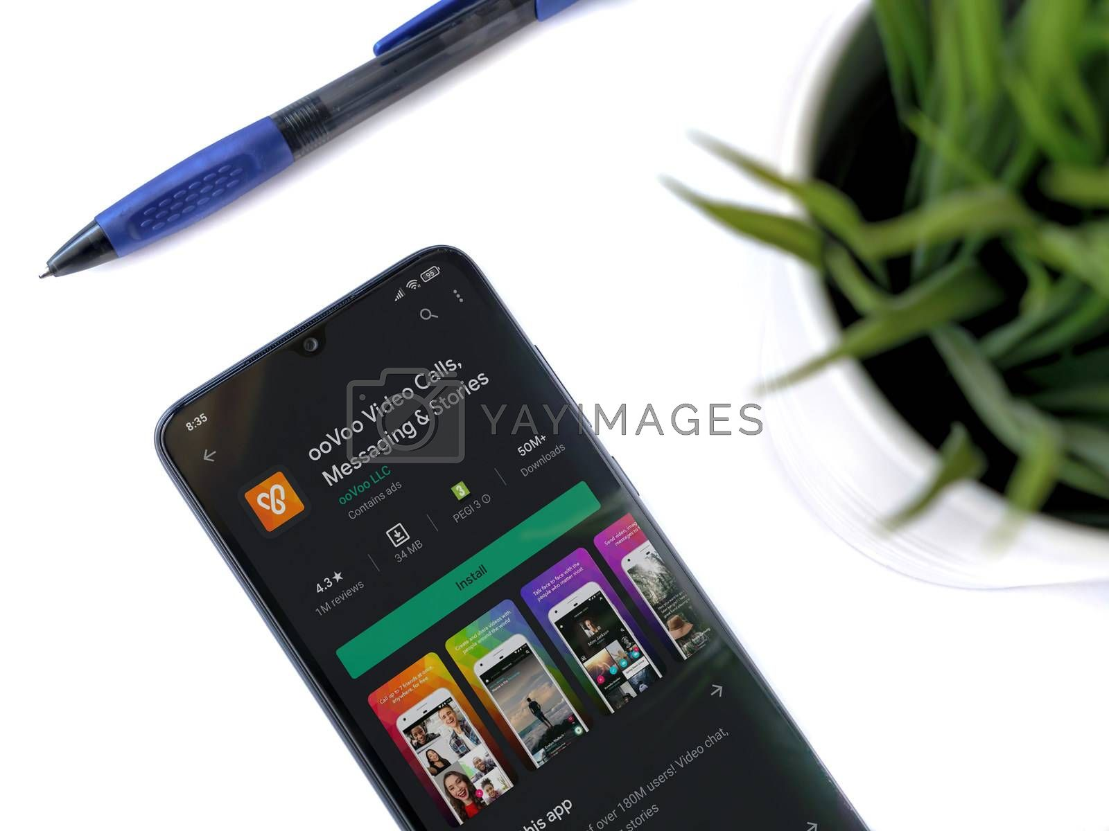 Lod, Israel - July 8, 2020: Modern minimalist office workspace with black mobile smartphone with ooVoo app play store page on white background. Top view flat lay with copy space.