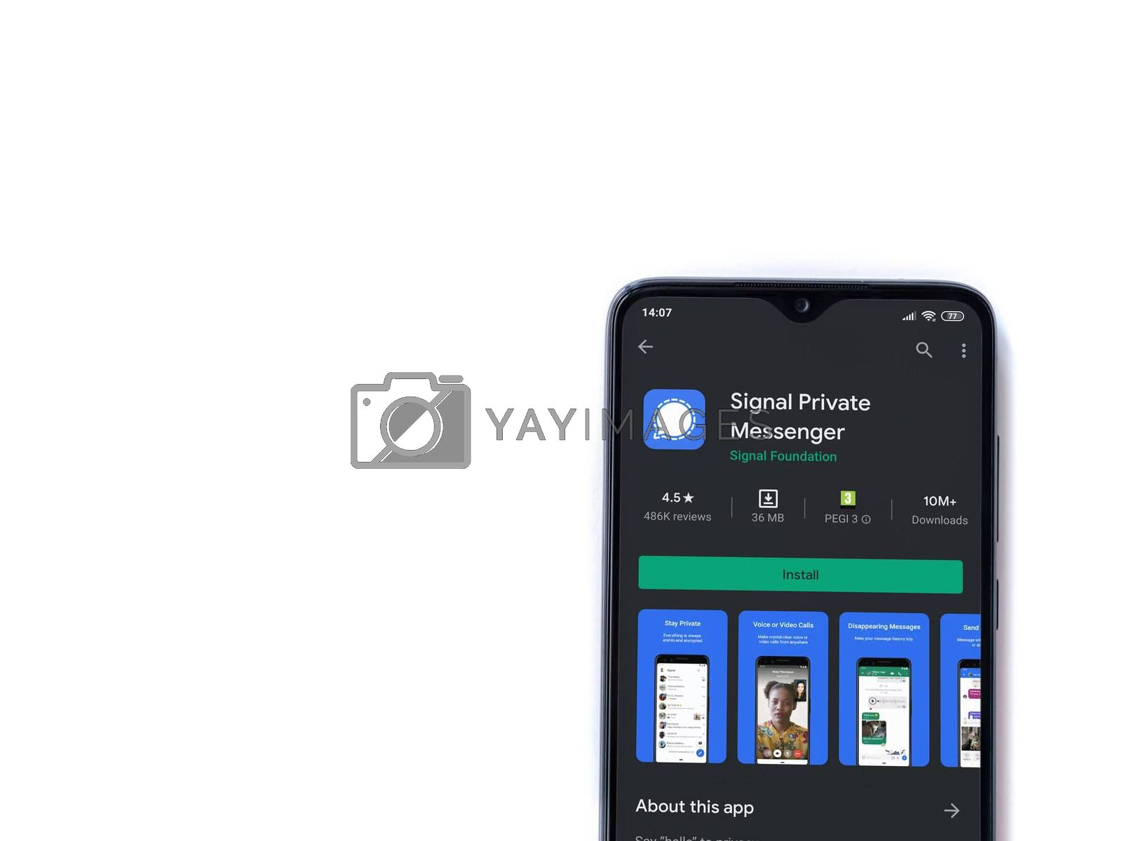 Lod, Israel - July 8, 2020: Signal Private Messenger app play store page on the display of a black mobile smartphone isolated on white background. Top view flat lay with copy space.