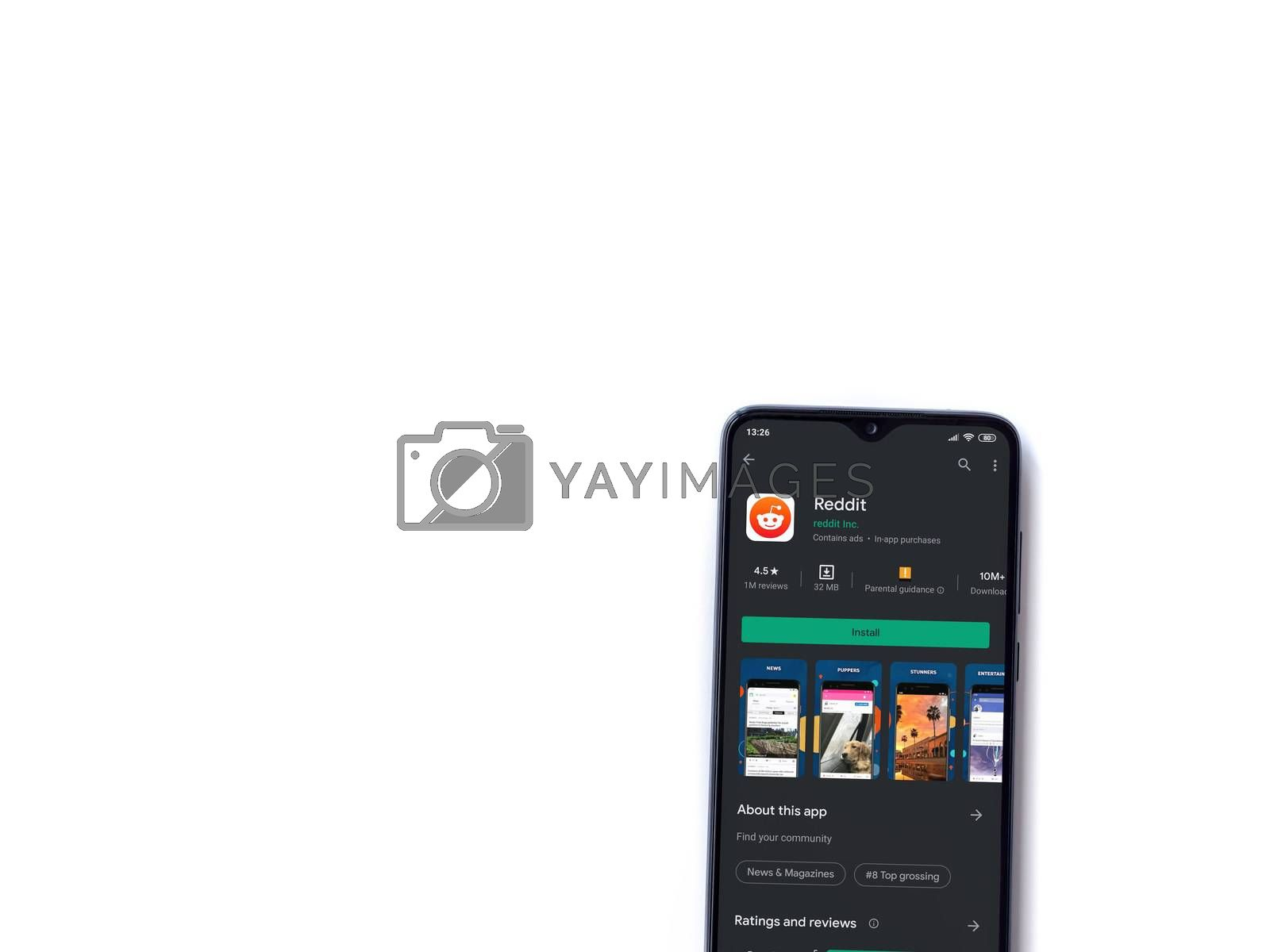 Lod, Israel - July 8, 2020: Reddit app play store page on the display of a black mobile smartphone isolated on white background. Top view flat lay with copy space.