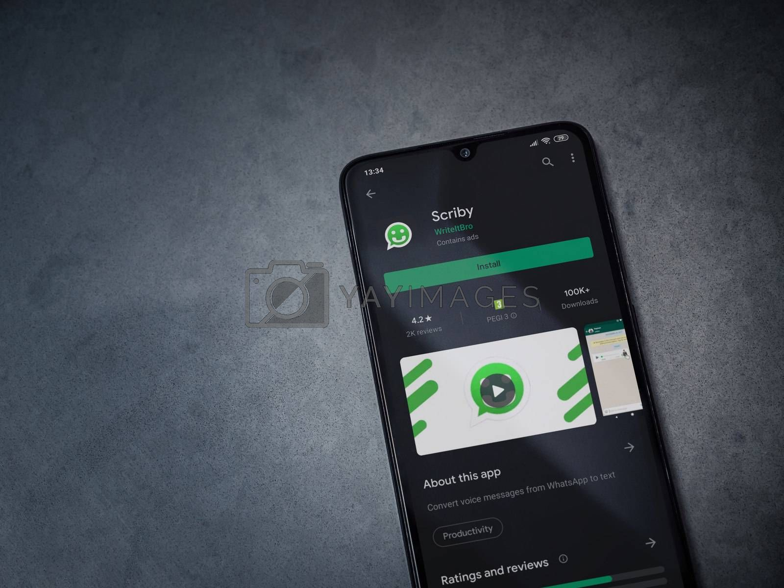Lod, Israel - July 8, 2020: Scriby app play store page on the display of a black mobile smartphone on dark marble stone background. Top view flat lay with copy space.