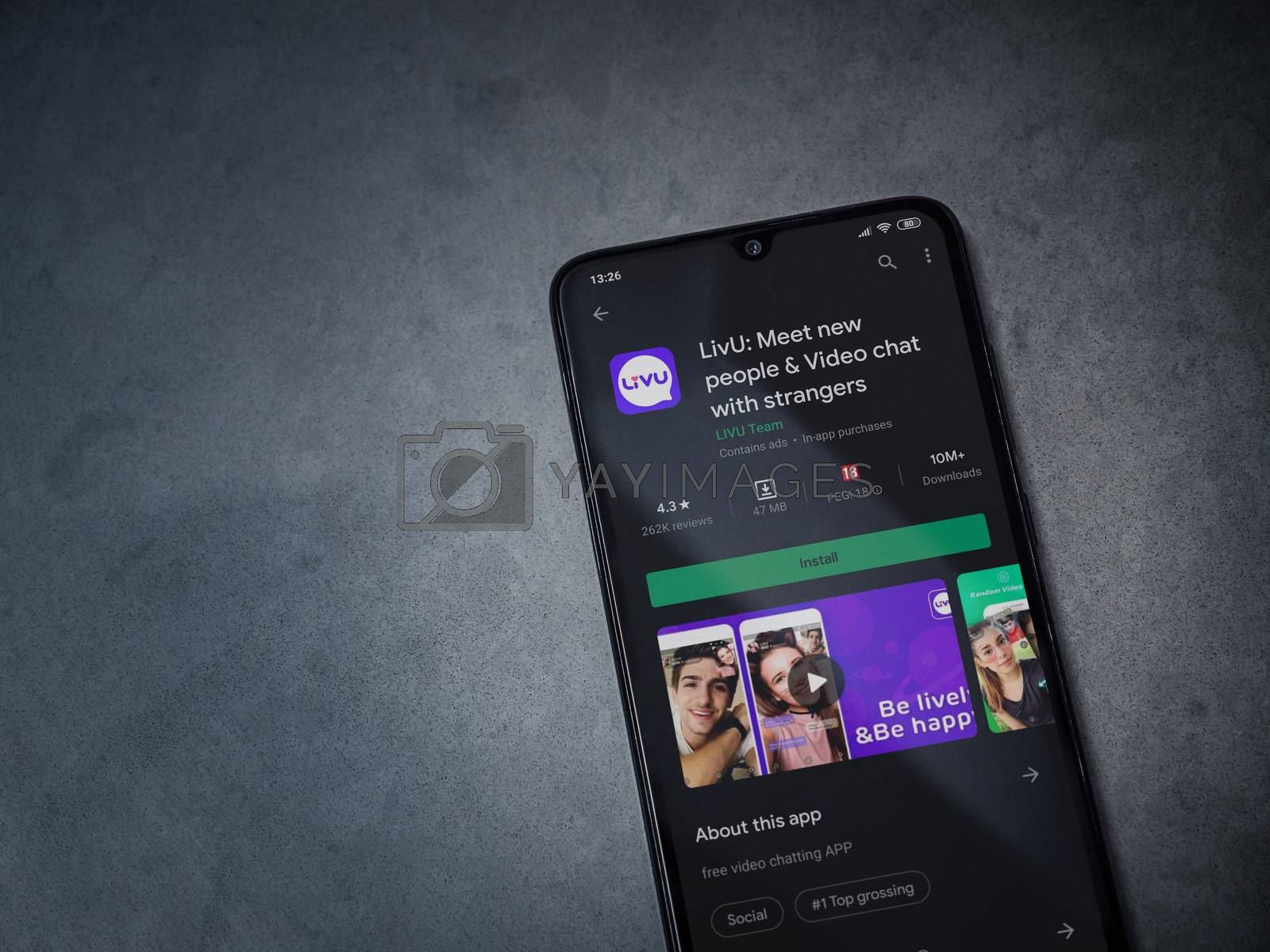 Lod, Israel - July 8, 2020: LiveU app play store page on the display of a black mobile smartphone on dark marble stone background. Top view flat lay with copy space.