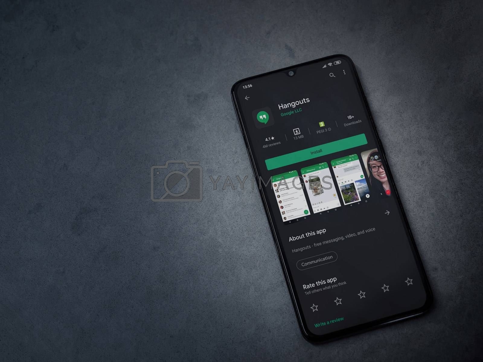 Lod, Israel - July 8, 2020: Hanghouts app play store page on the display of a black mobile smartphone on dark marble stone background. Top view flat lay with copy space.