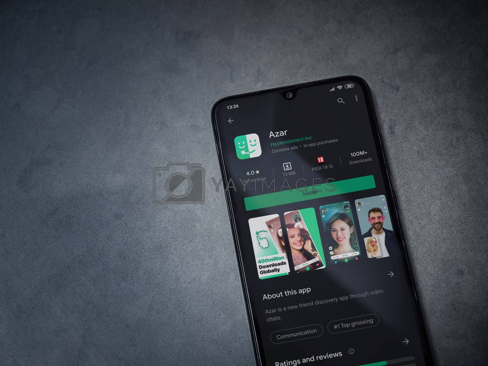 Lod, Israel - July 8, 2020: Azar app play store page on the display of a black mobile smartphone on dark marble stone background. Top view flat lay with copy space.