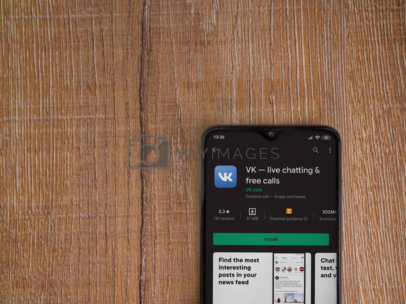 Lod, Israel - July 8, 2020: VK app play store page on the display of a black mobile smartphone on wooden background. Top view flat lay with copy space.