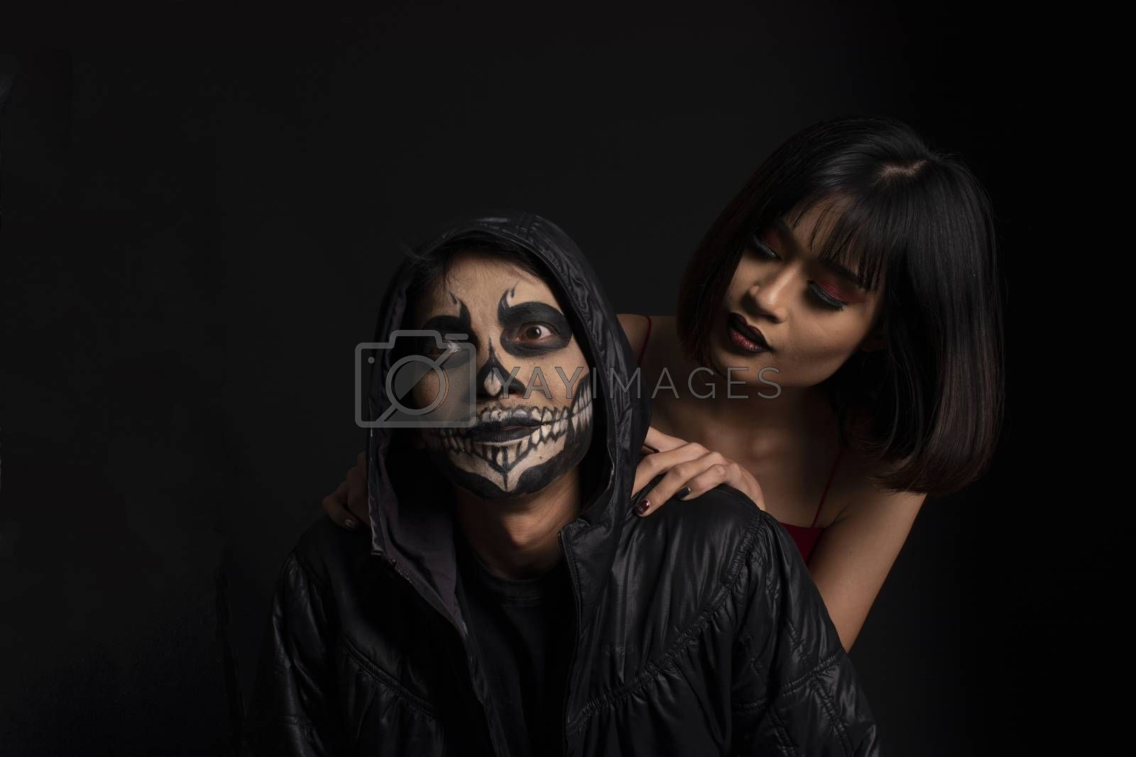 Southeast asian man with skull face makeup and woman on black background, portrait photography
