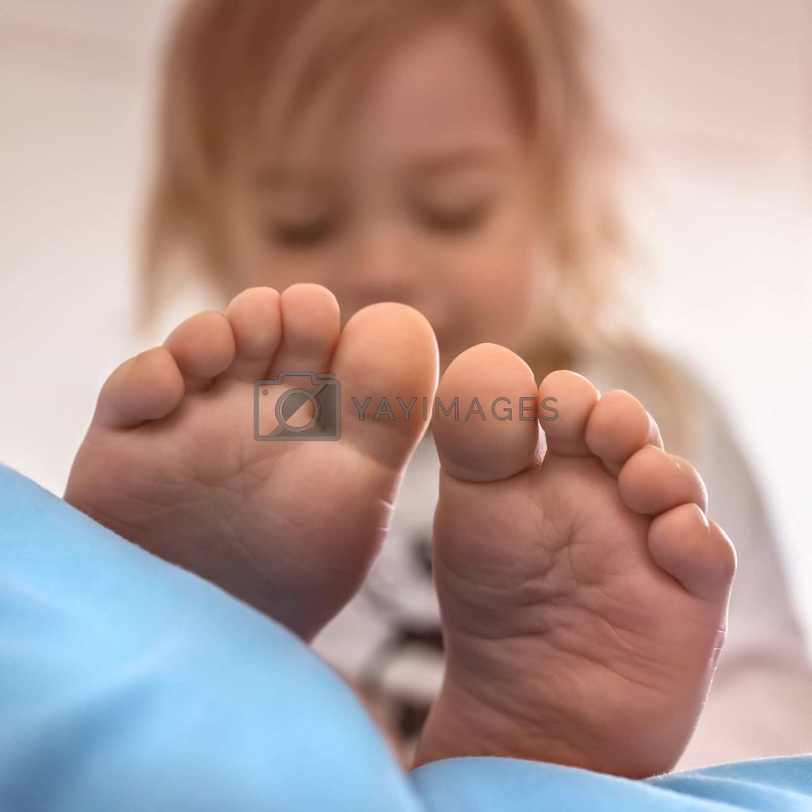 Sweet Child in the Bed. Baby Waking Up in the Morning. Selective Focus Portrait of a Toddler with Bare Feet in the Foreground. Happy Healthy Childhood.