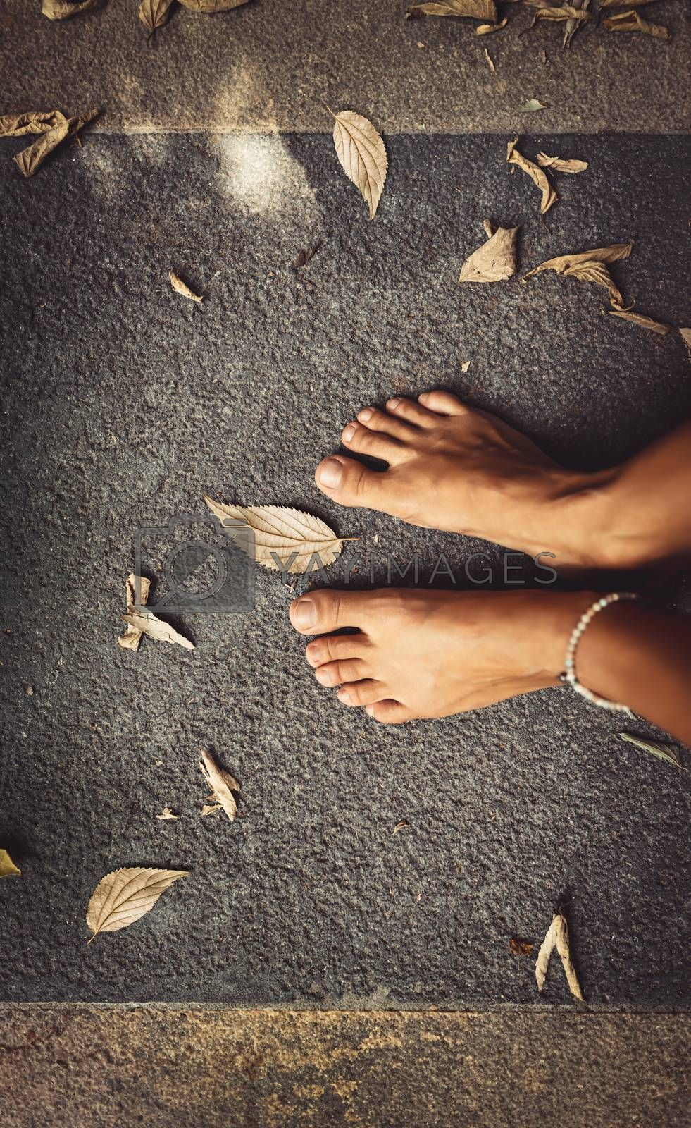 Welcome Fall Background. Closeup Concept Photo of a Barefoot Women Feet and Dry Leaves. Autumn Season Theme. Summer is Over.