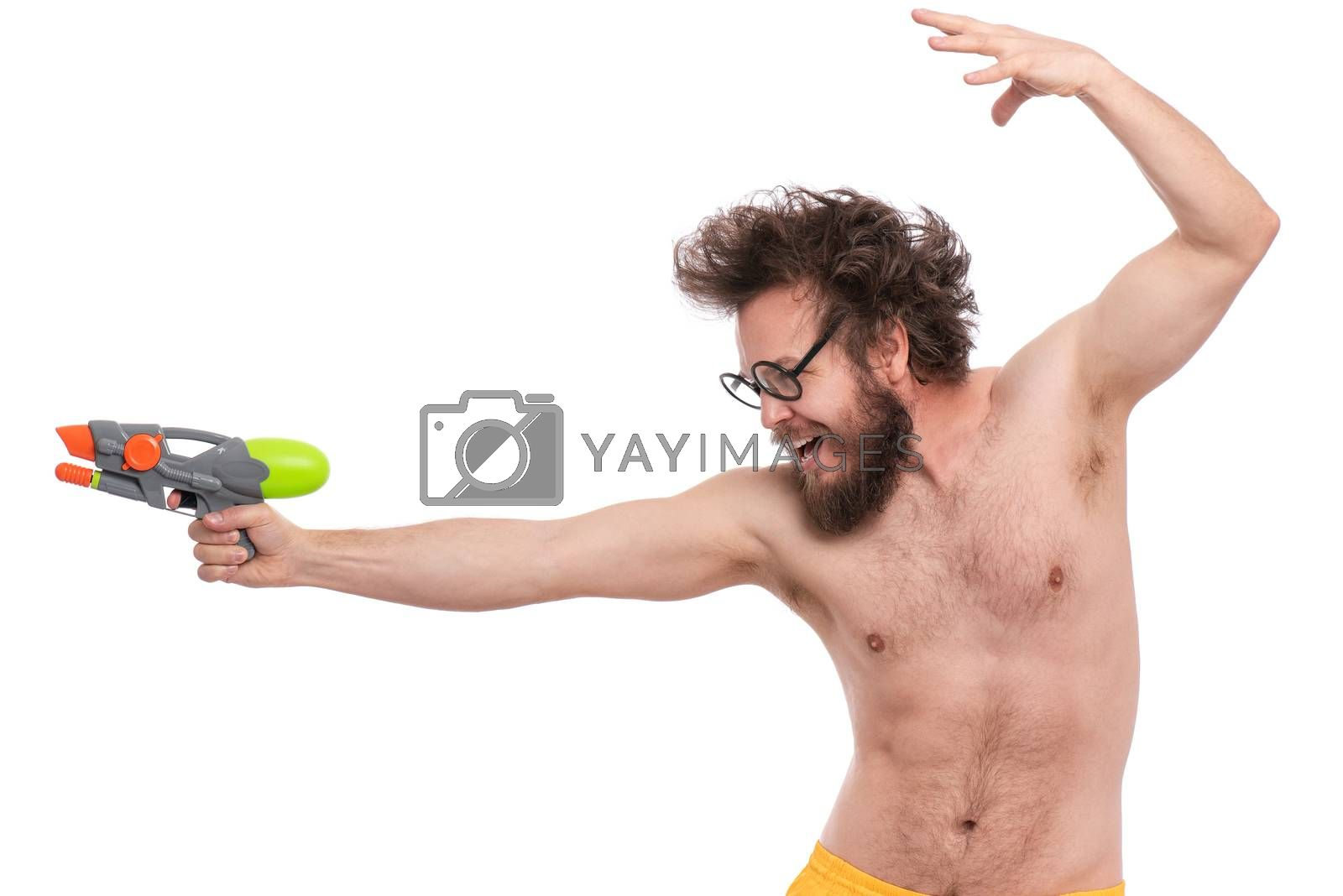 Crazy bearded Man with funny Haircut in eye Glasses, ready for fun at sunny beach. Happy and silly tourist, isolated on white background. Cheerful naked man holding Water Gun.