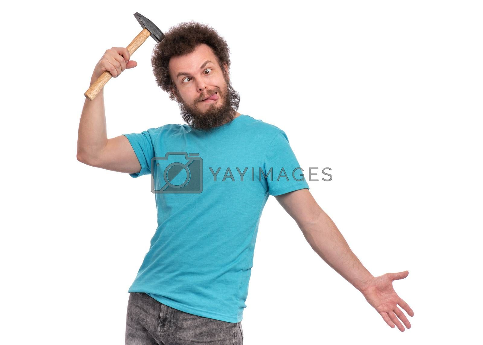 Crazy bearded Man is hitting him self in head with Hammer and making grimace - Silly face. Guy with funny Curly Hair, isolated on white background. Emotions, and signs concept.