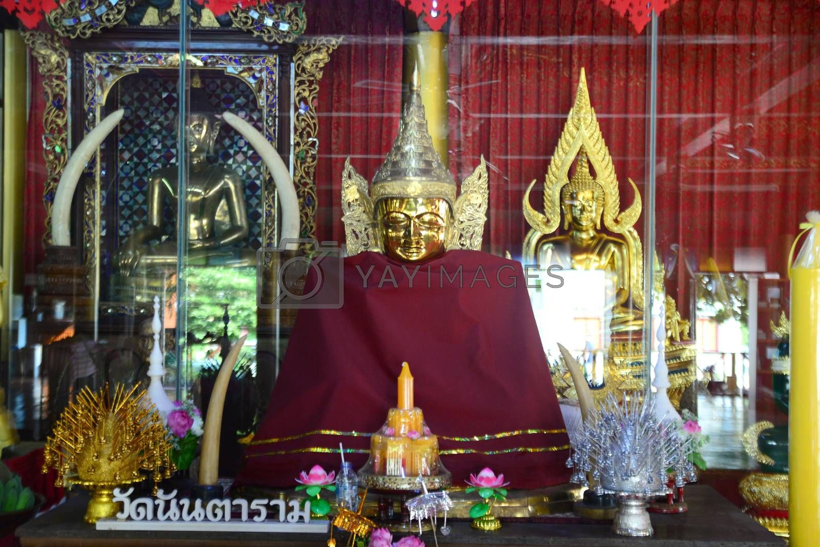 Phayao, Thailand  – 21 December, 2019 : Wat Nantaram, the principle Buddha image crafted from teak wood in the Viharn (sermon hall) of teak wood, exquisitely crafted in traditional Tai Yai style