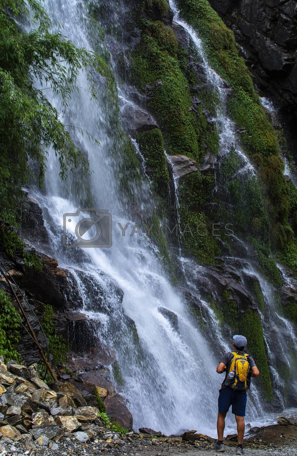 Man standing to look at waterfall, travel photography