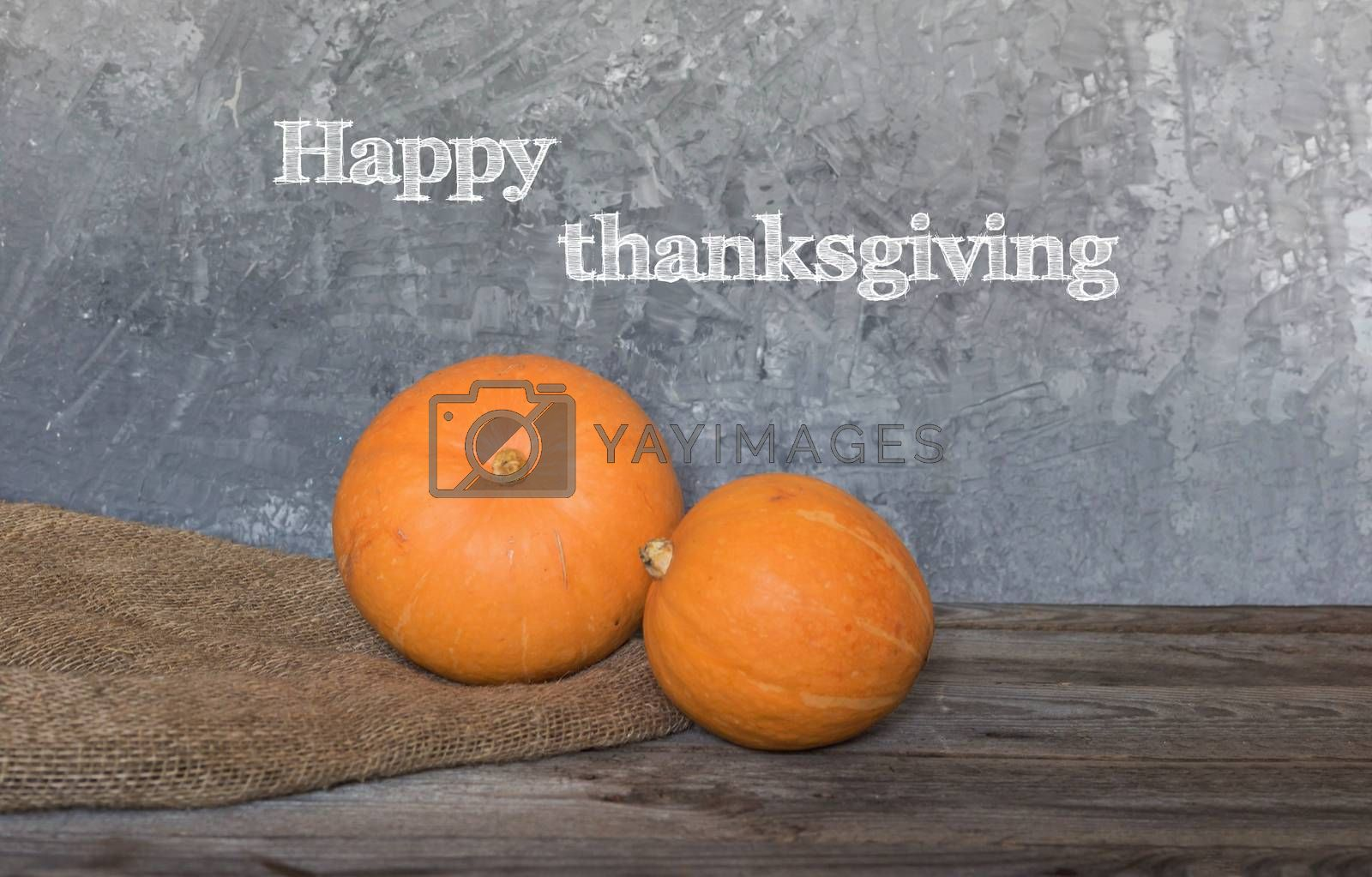 Happy Thanksgiving greeting text with colorful pumpkins over dark wooden and Blackboard background