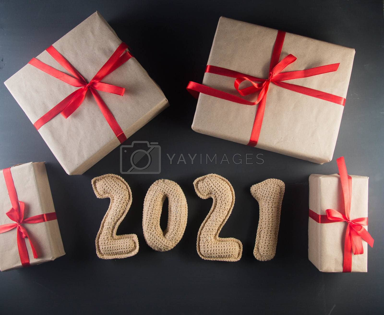 Christmas background with chroched 2021 number and craft paper gift boxes by galinasharapova
