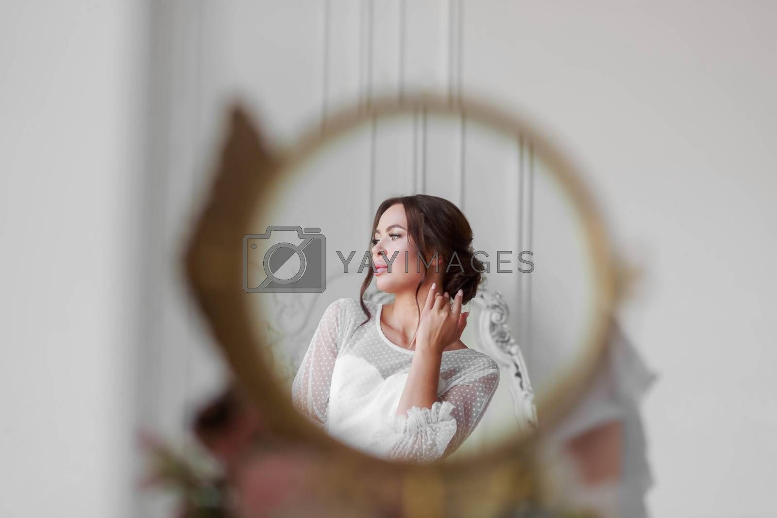 Portrait of the bride in a white wedding dress in a beautiful round mirror.
