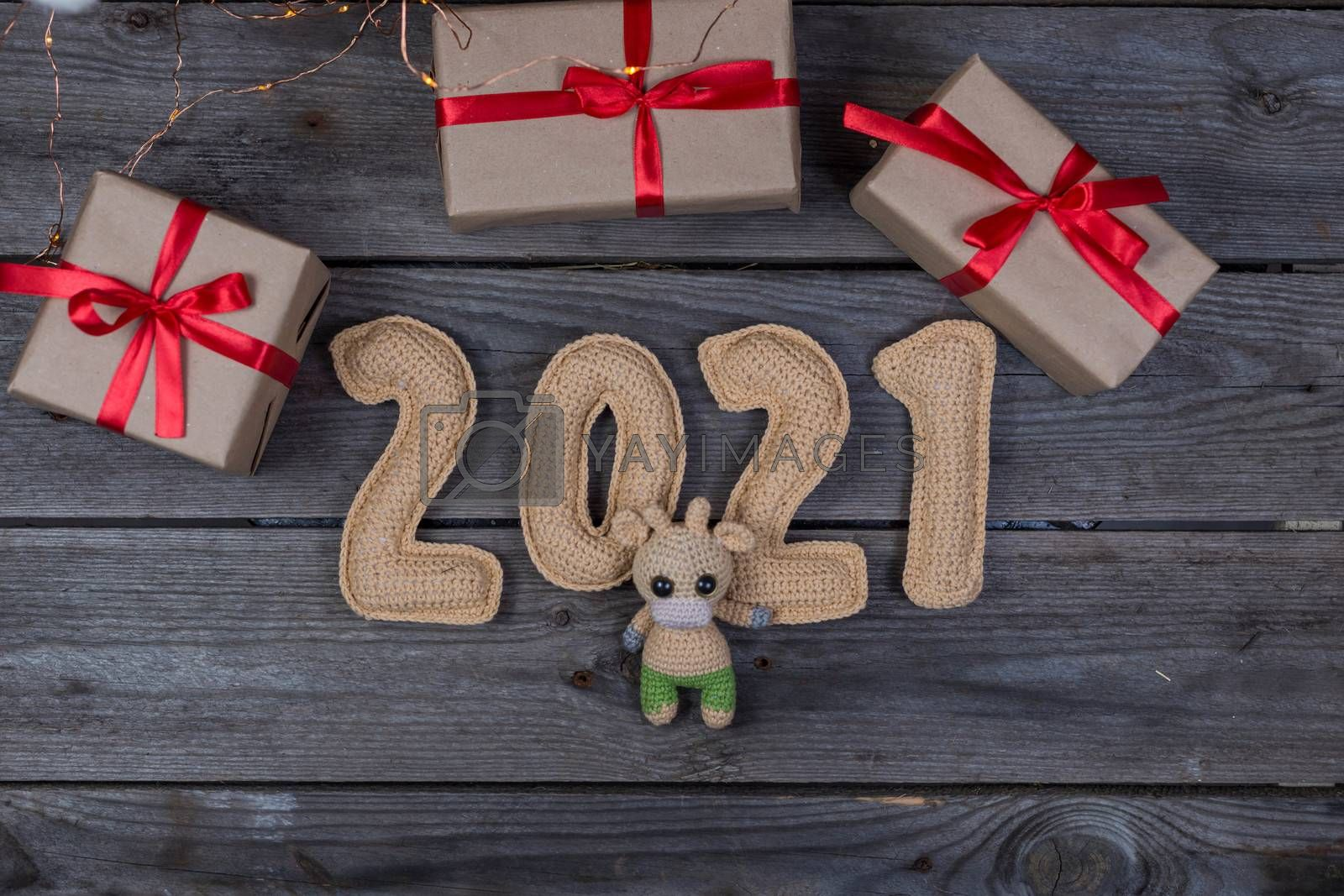 Christmas background with crocheted toy bull and numbers 2021
