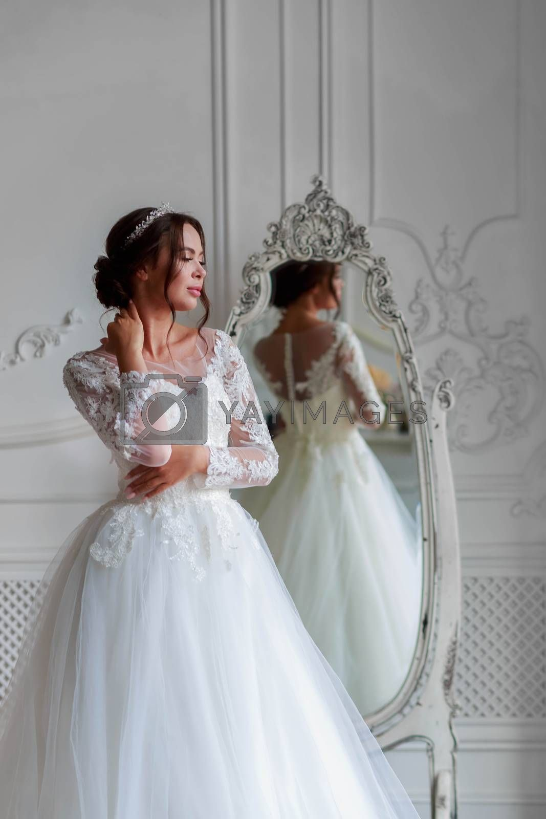 Portrait of a bride in a white wedding dress looks attentively aside.