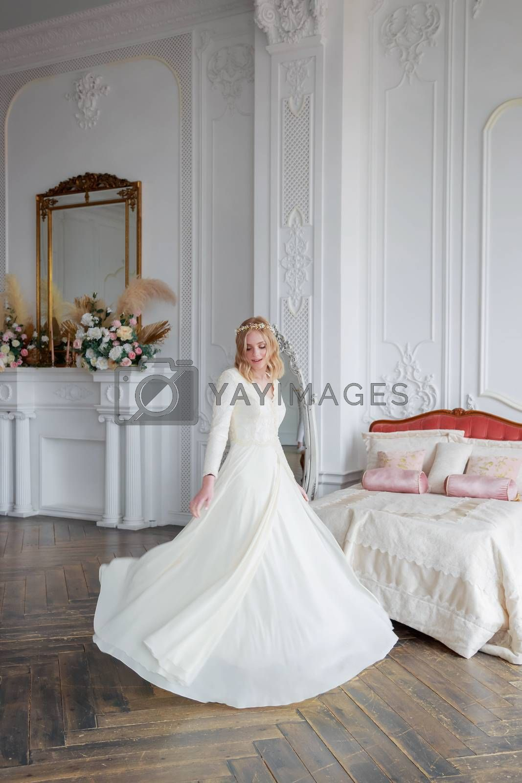 Full-length portrait of a bride in a beautiful lace wedding dress in the interior of a white studio
