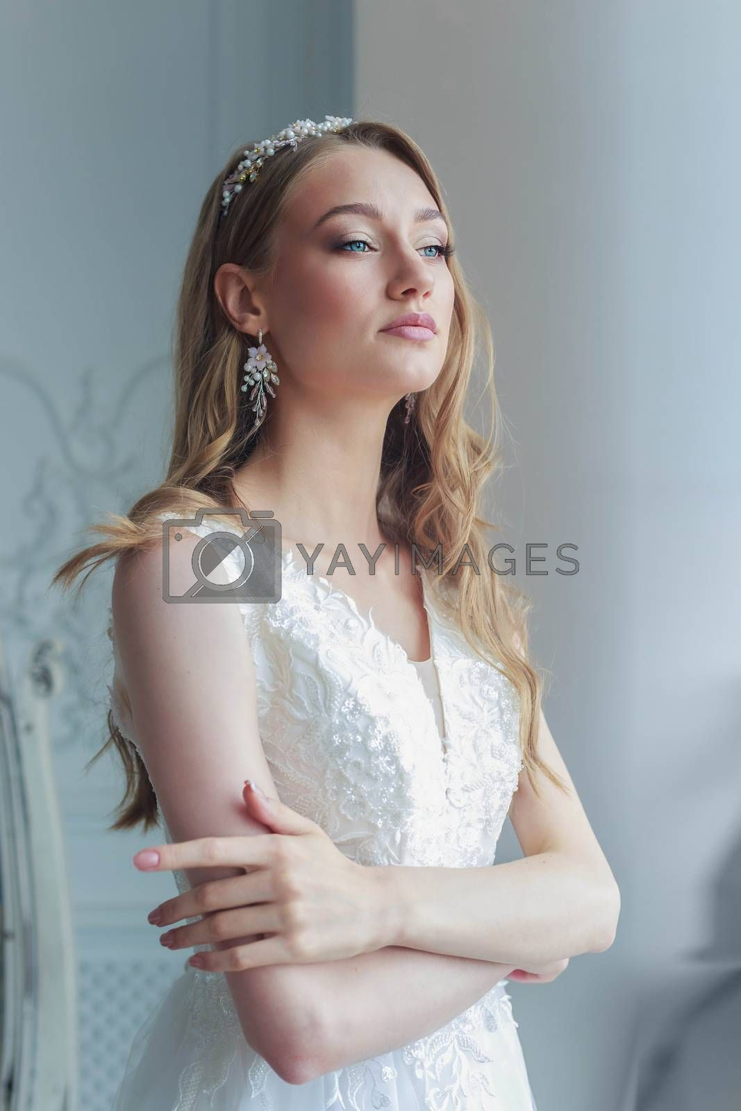 Close-up portrait of a bride in a white wedding dress looks attentively aside.