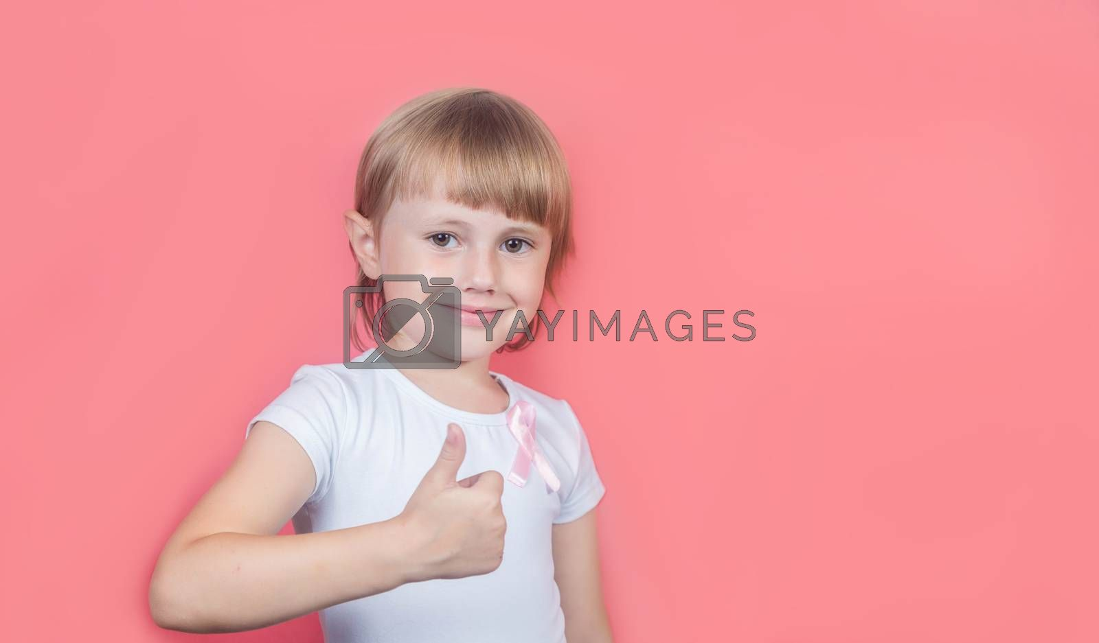 .Little girl showing thumb up wearing white t-shirt and pink breast cancer awareness ribbon