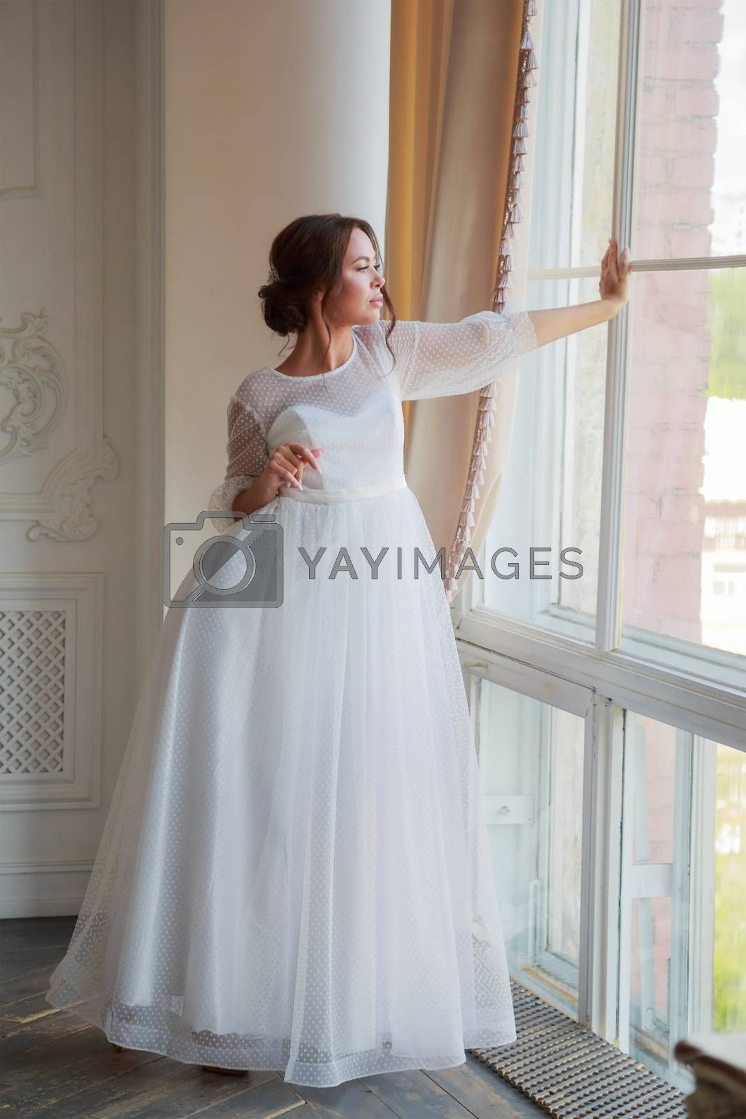 Full-length portrait of the bride in a white wedding dress by the window.