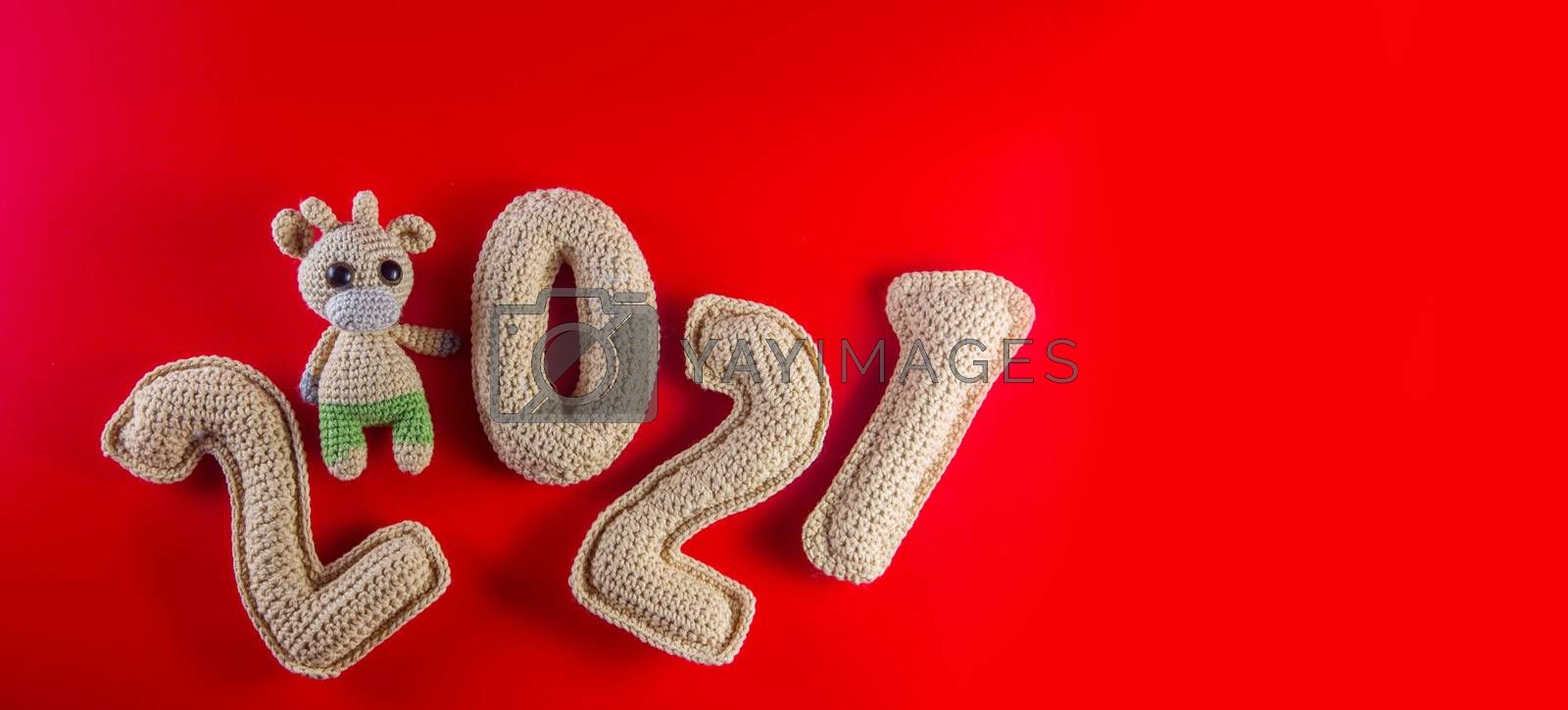 Cristmas background with knitted toy bull symbol of chinese new year 2021 by galinasharapova