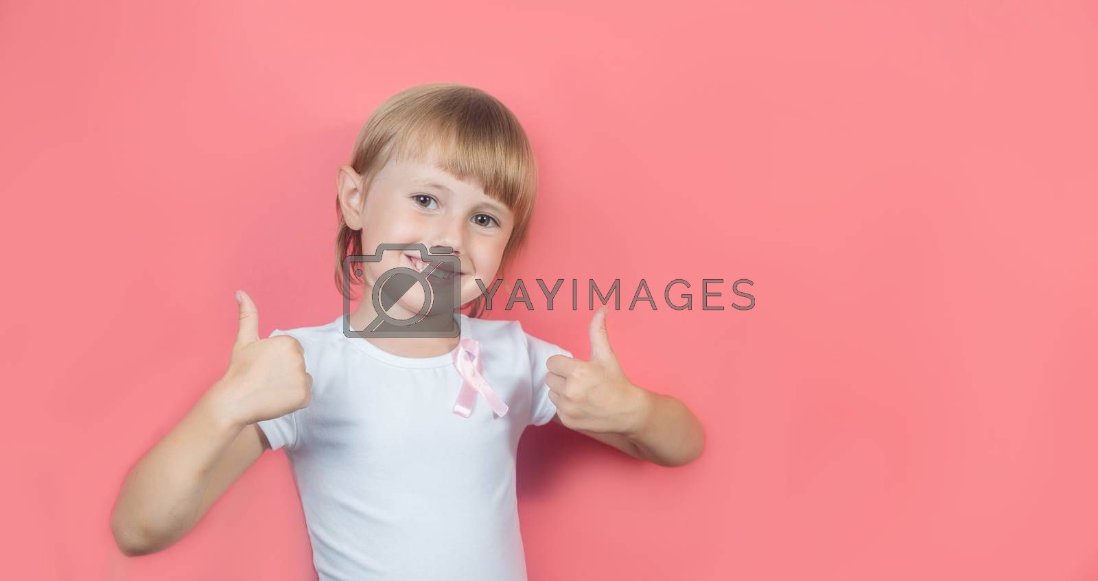 .Little girl showing two thumbs up in white t-shirt and with pink breast cancer awareness ribbon