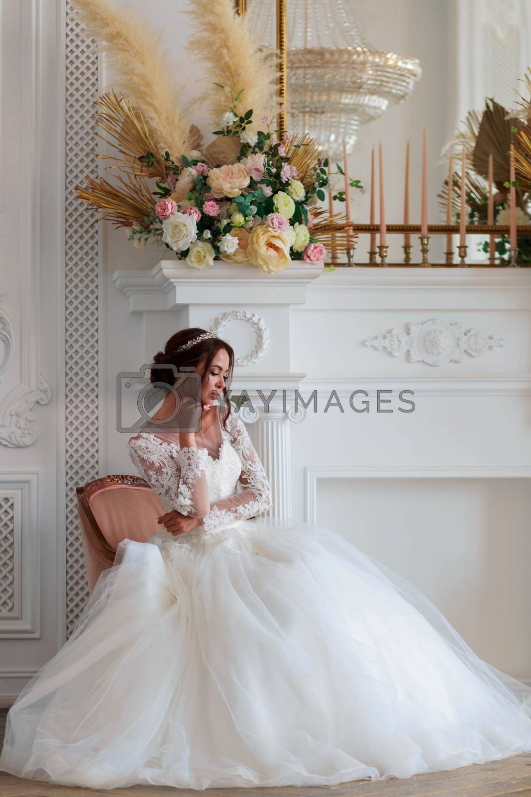 The bride in a white wedding dress sits thoughtfully in a chair waiting for the groom.