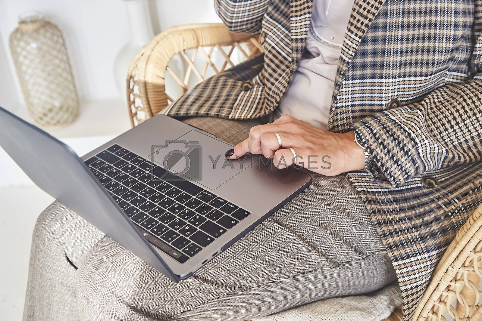 Woman businessman working on laptop in a comfortable rattan wicker chair in the beautiful interior of her country house