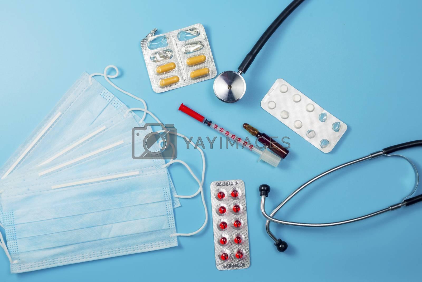Covid-19, coronavirus treatment. Pills, stethoscope and medical masks on blue background.