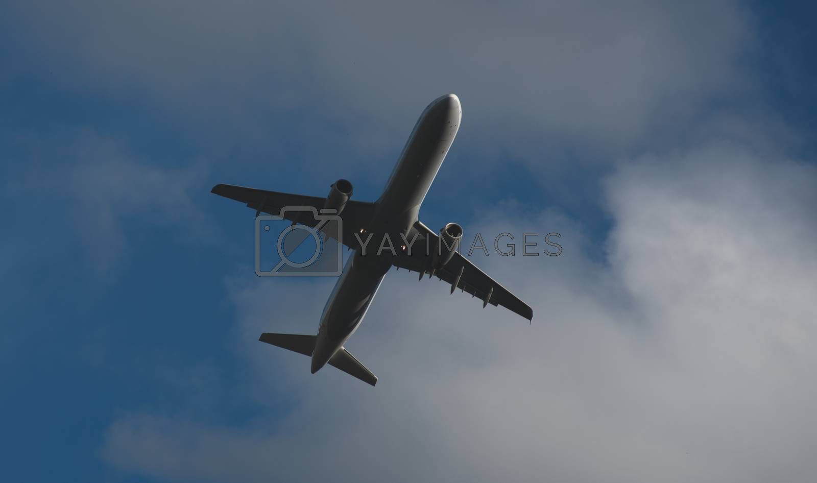 Silhouette of a plane taking off against the blue sky