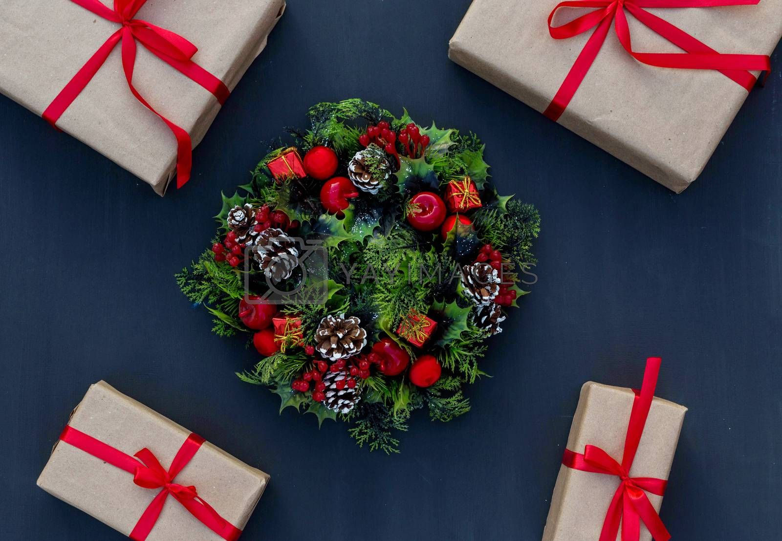 .New year wreath and gifts tied with a red ribbon on a chalk board