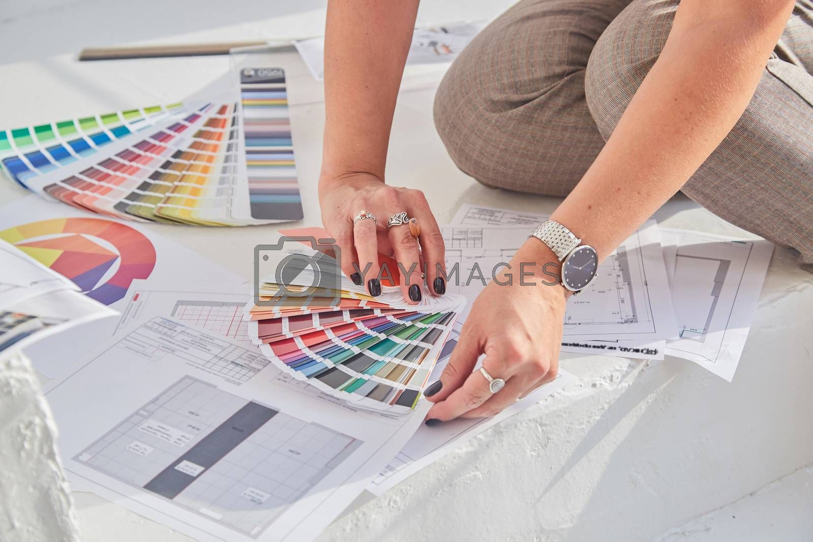 Close-up view of interior designer woman's hands working with color palette and interior plans for a new project with soft focus..