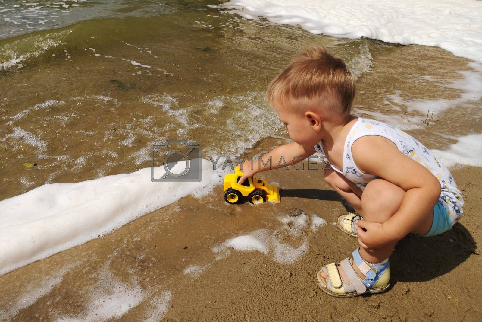 A cute little boy plays on the shore of the lake with a bright yellow toy car in the foam of the lake.Summer kids holiday concept. Rest on the shore.
