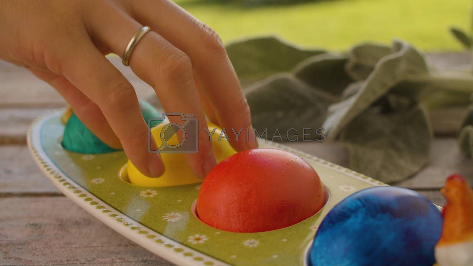 Close up hand taking a colored yellow Easter egg from an egg box placed on wooden table in the garden. Easter celebration