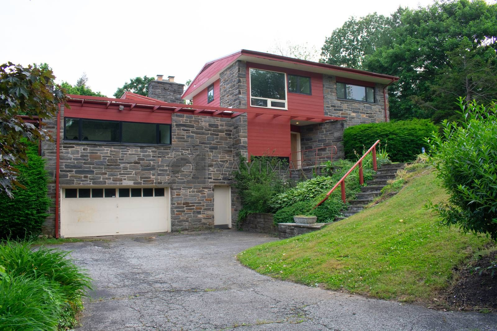 A Modern Cobblestone House With a Red Trim and a Red Roof and Driveway