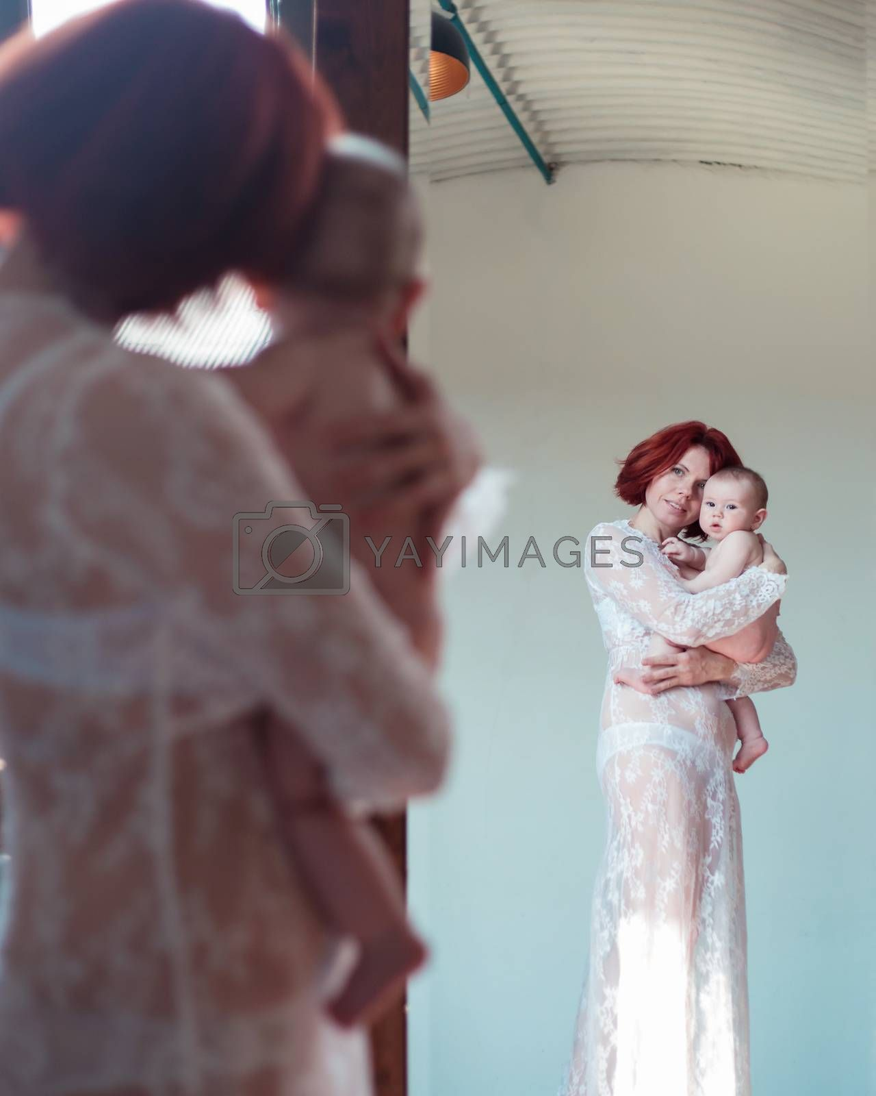 Mom holds the baby in her arms while standing in front of the mirror
