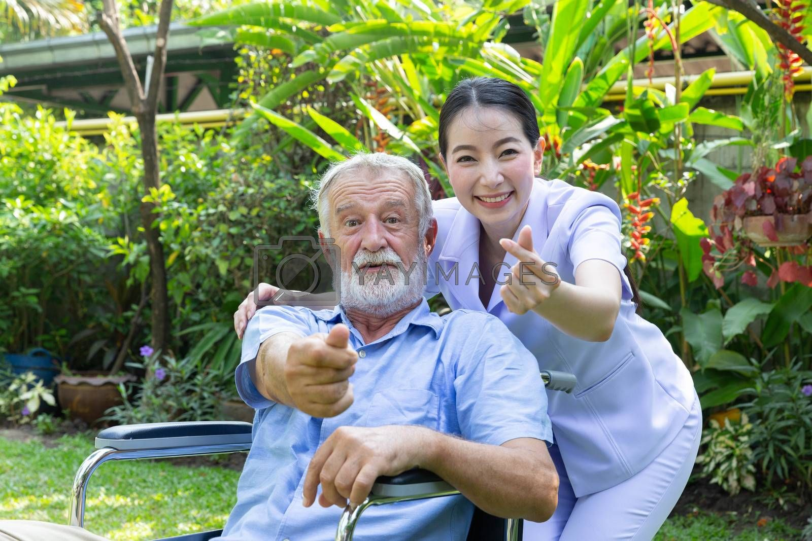 A nurse take care a senior male and give mini heart on wheelchair in his garden at home