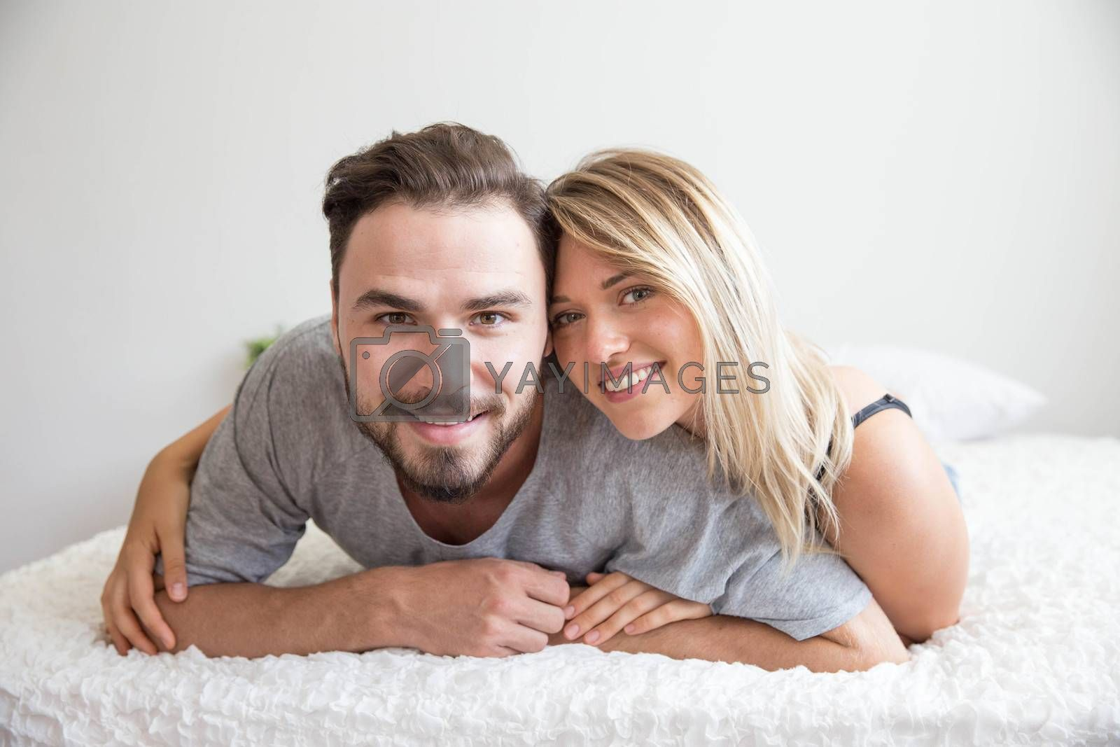 A couple in bed look at camera and smile with happy lover