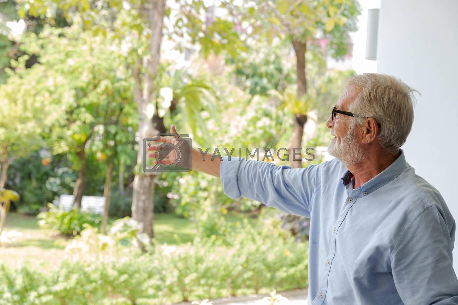 A senior retirement grandfather enjoy the gardan in his house backyard