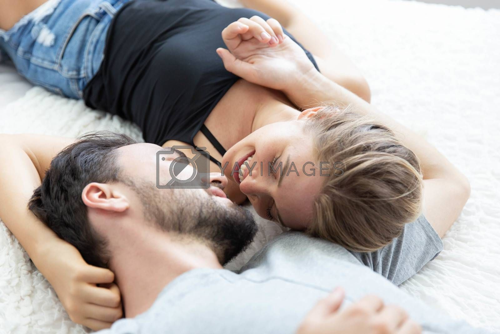 Lovely happy couple in love, smile, and kiss each other on their bed in the bedroom