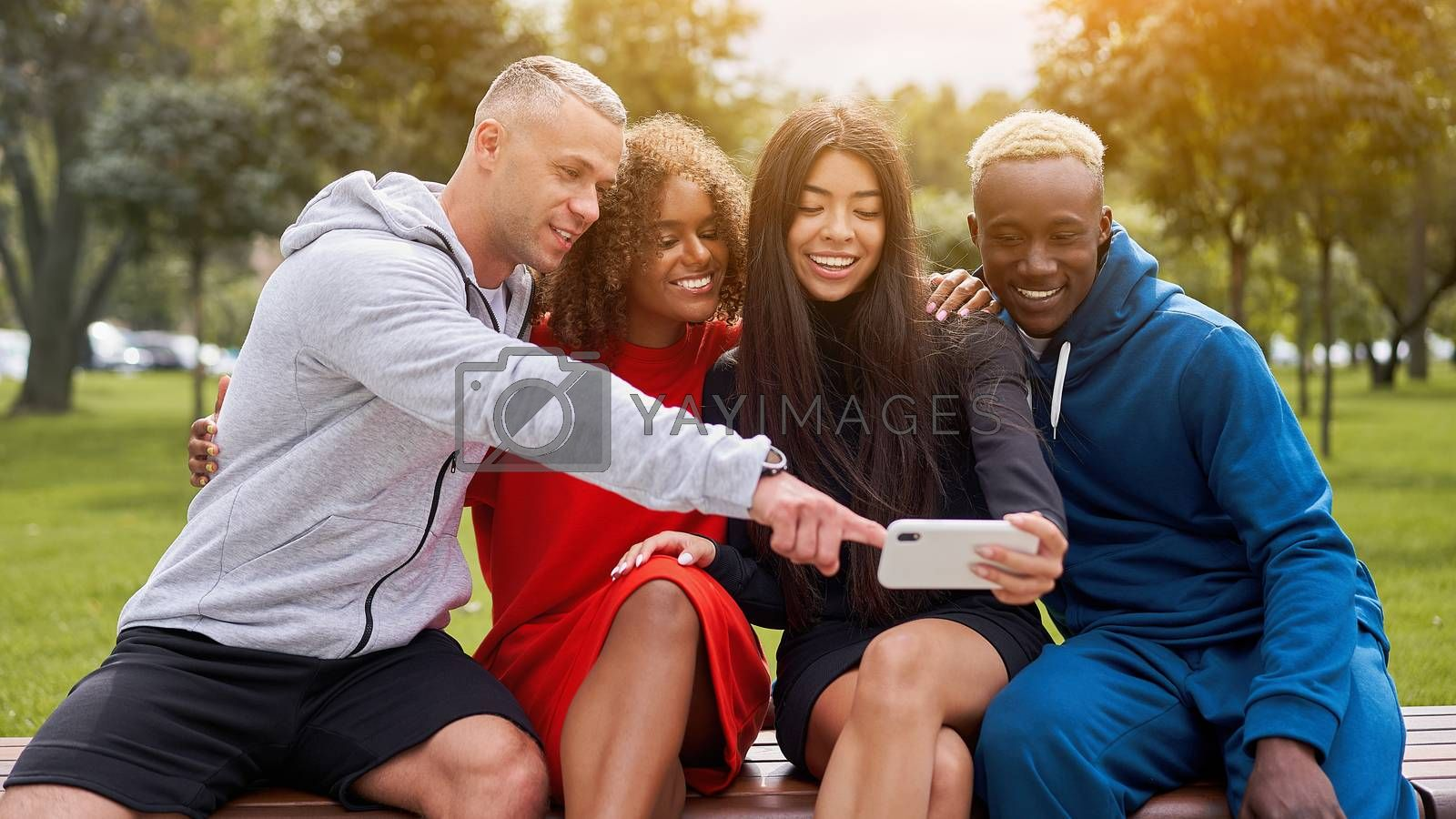 Multi ethnic friends outdoor looking smartphone screen. Diverse group people Afro american asian caucasian spending time together Multiracial male female student sitting bench park outdoors