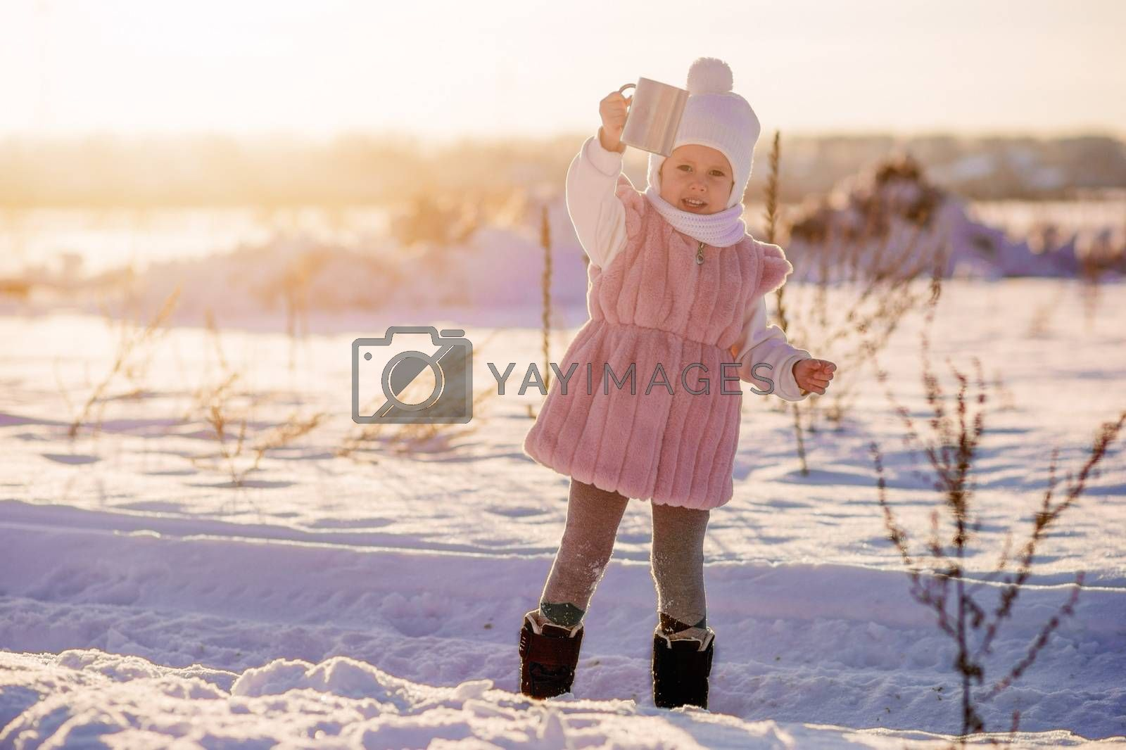 .A little girl stands with a mug of hot chocolate in the middle of a field by galinasharapova