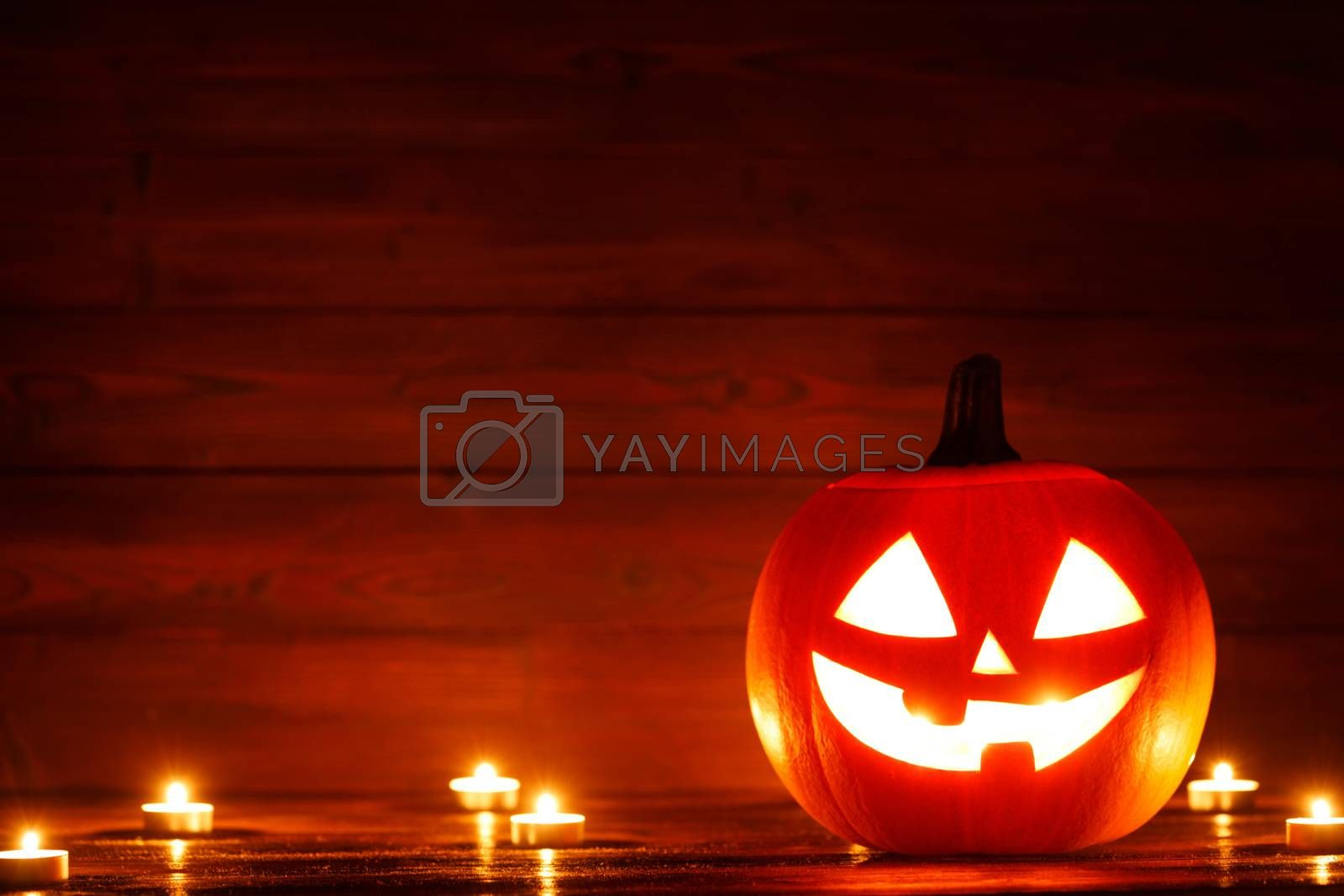 Halloween Jack o Lantern pumpkin head and burning candles on wooden background