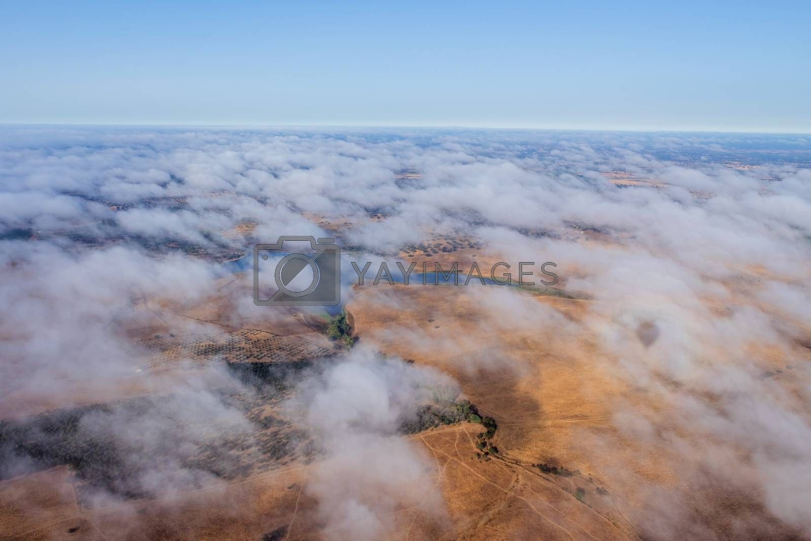 Hot air balloon in the Alentejo region, above the clouds and the fields. Portugal.