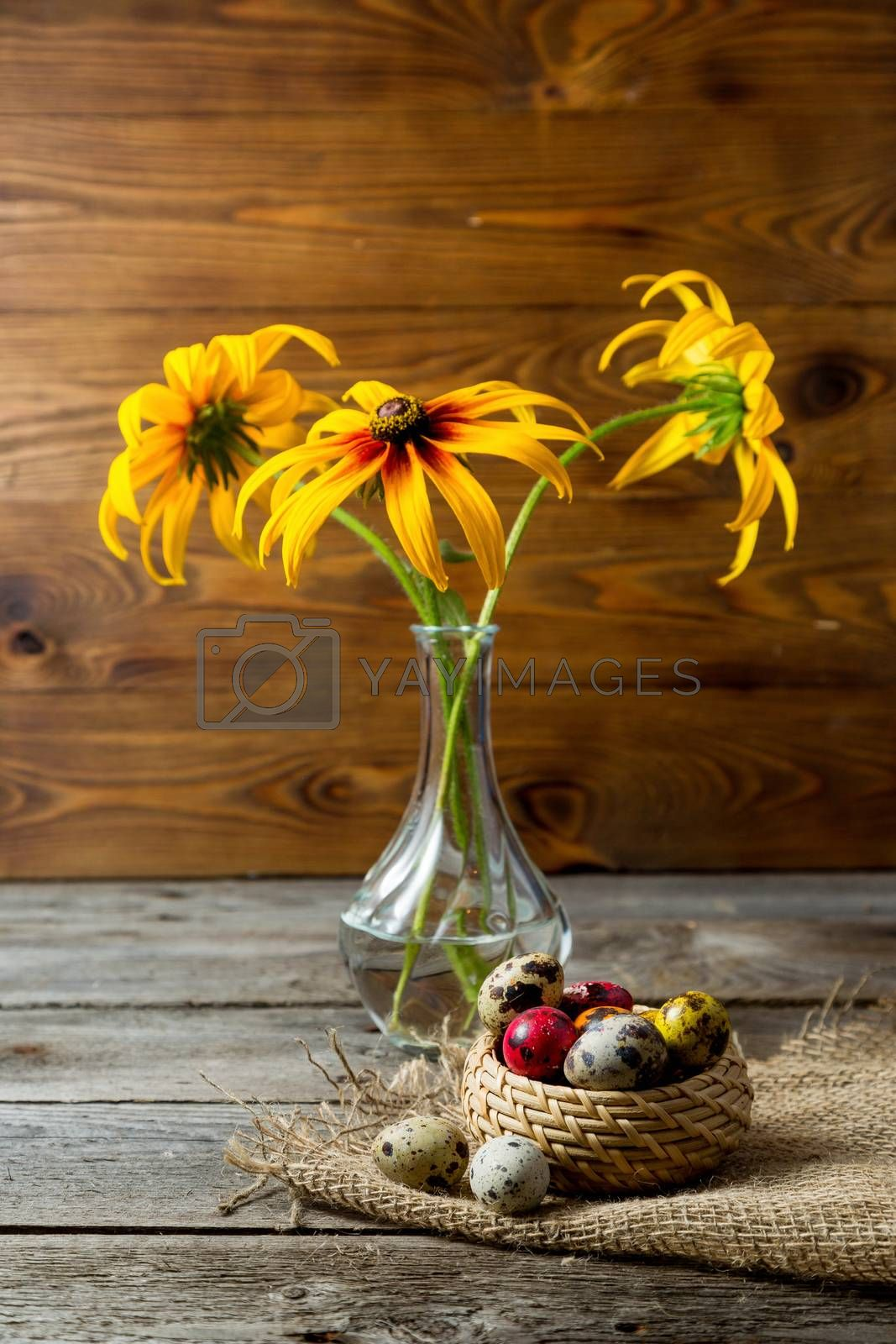 Multi-color dyed Hand painted easter eggs in wicker basket on burlap napkin on wooden background . Still life with flowers. Easter background with space for a text.