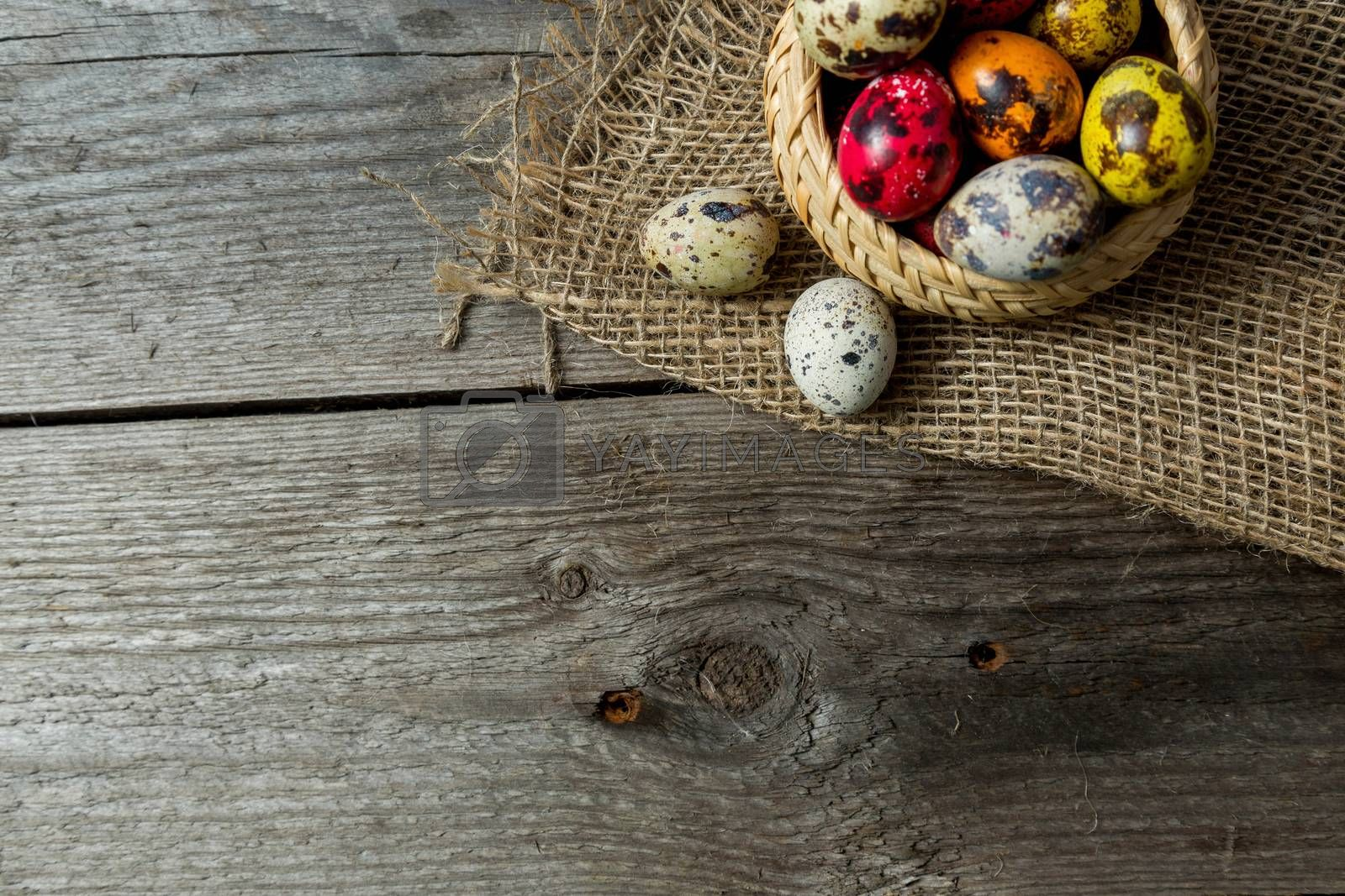 Multi-color dyed Hand painted easter eggs in wicker basket on burlap napkin on wooden background. Easter background with space for a text.